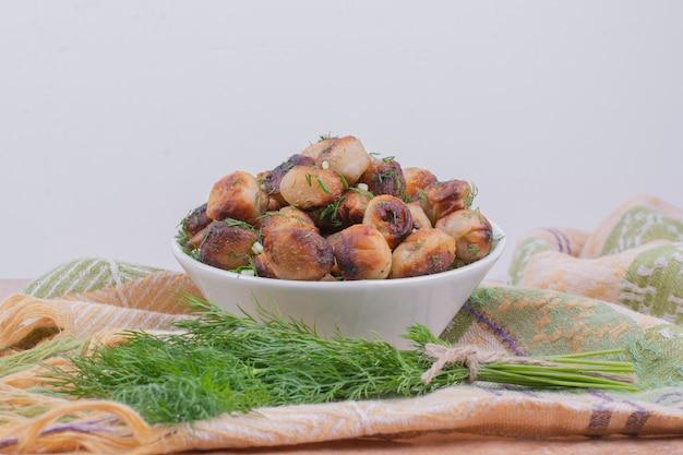 Khinkali caucasico fritto con erbe in una ciotola bianca