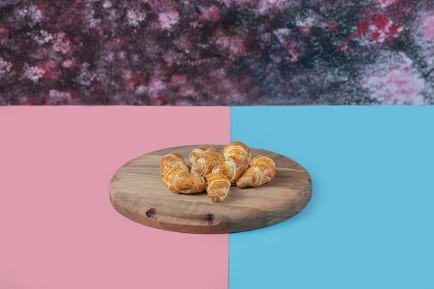 Жареные кавказские печенья мутаки на деревянной доске на розовом синем столе.
