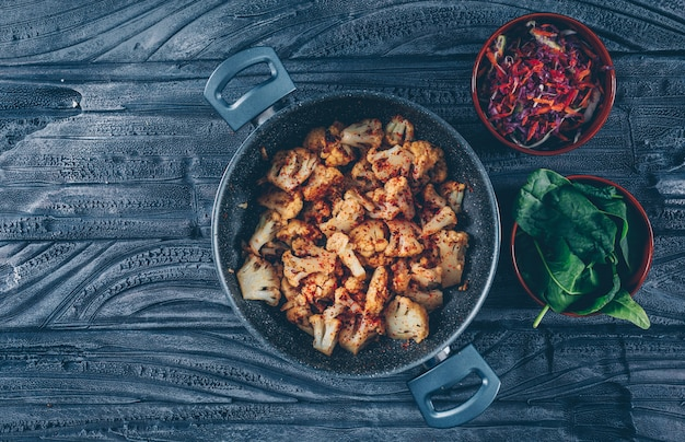 Fried cauliflower in a pot with vegetable salad, green top view on a dark wooden background. space for text