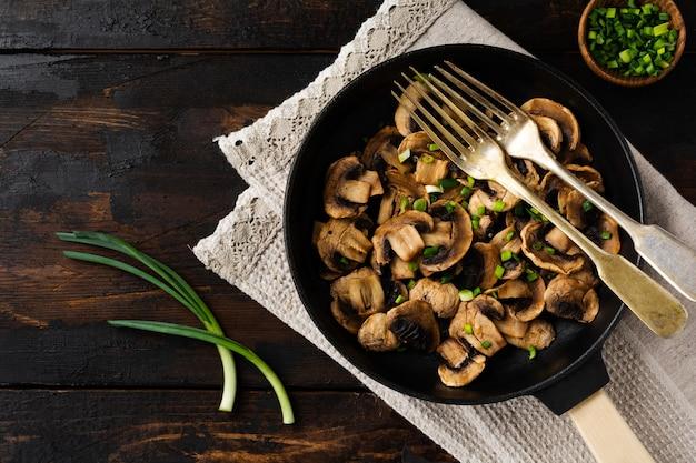 튀김에 대한 오래 된 어두운 나무 소박한에 주철 오래 된 냄비에 튀긴 샴 피뇽 버섯