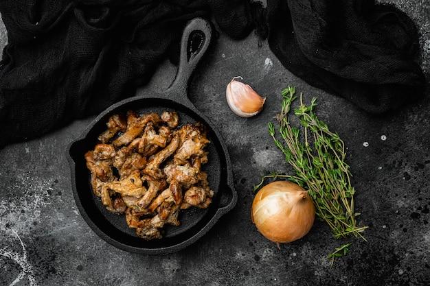 Набор жареных лисичек на чугунной сковороде на черном фоне темного каменного стола, плоский вид сверху