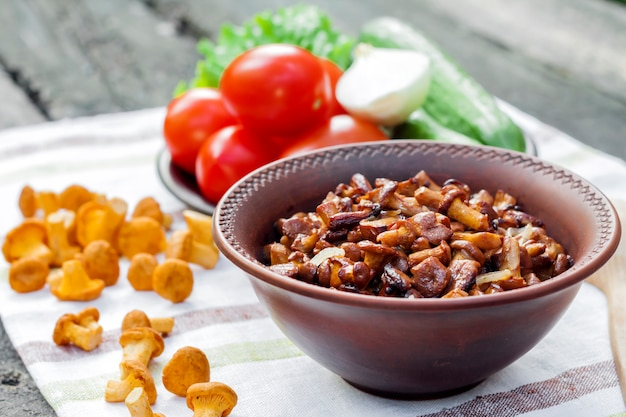 Fried chanterelles with onion in rustic bowl and plate with fresh vegetables for salad