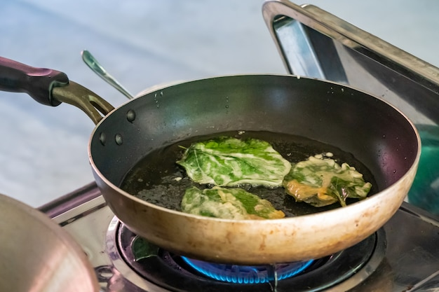 Fried chaplu leaf (wild betel leafbush) in the pan for eat with traditinal thai food.