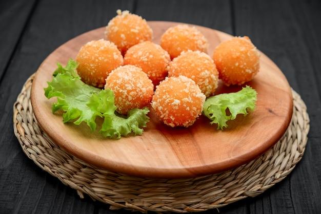Жареный сырный шарик, сырные наггетсы на деревянной тарелке