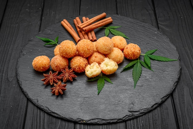 Fried cheese ball, cheese nuggets on a wooden plate
