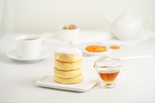 Fried cheese cakes, sweet cheese pancakes on white plate on white background. home tea party