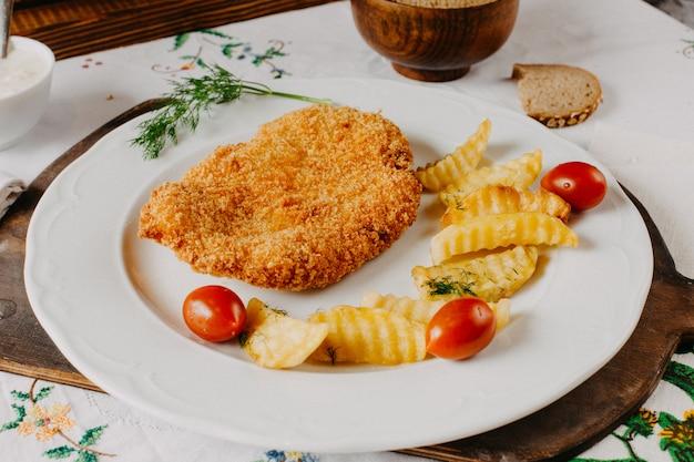 茶色の机の上の白い皿の中のジャガイモの赤いトマトと一緒にフライドチキン