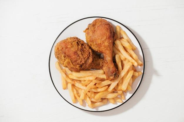흰색 배경에 격리된 흰색 접시에 프라이드 치킨과 감자튀김