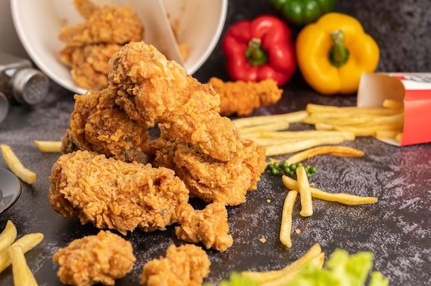 Жареный цыпленок и картофель на черном цементном полу.