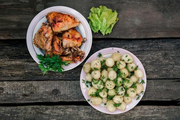 튀긴 닭고기와 어린 감자와 dill.simple 시골 요리 .wooden wall.top보기