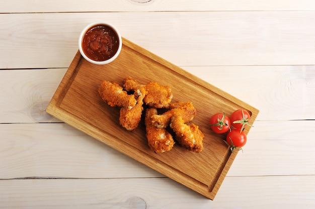 Fried chicken in breadcrumbs with ketchup, tomatoes