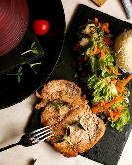 양상추 샐러드와 밥을 곁들인 튀긴 닭 가슴살