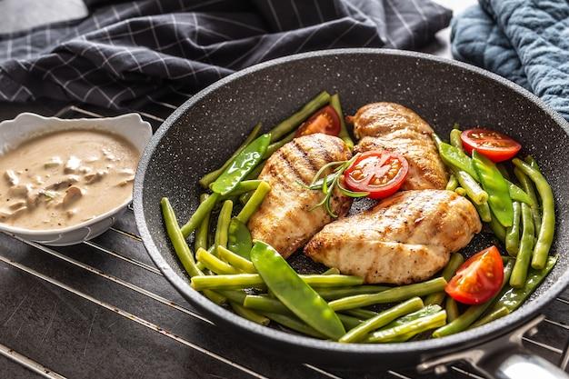 Жареные куриные грудки и овощи на сковороде со сливочно-грибным соусом на стороне, помещенные на черном фоне с полотенцем и прихватками.