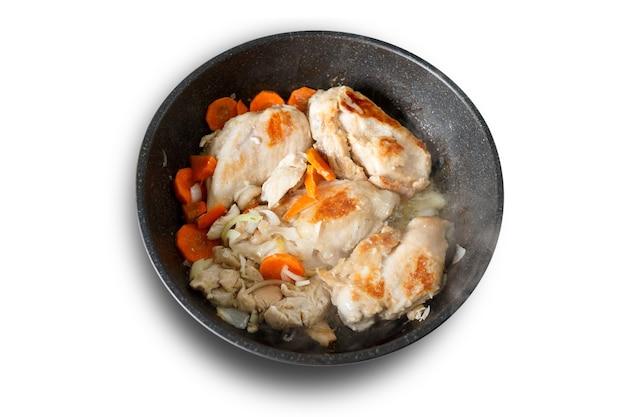 Ломтики жареной куриной грудинки на сковороде, изолированной на белом