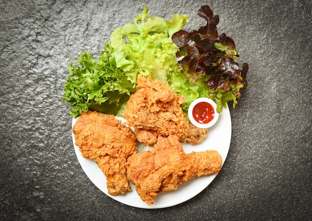 Fried chicken crispy kentucky on white plate with ketchup and salad lettuce vegetable