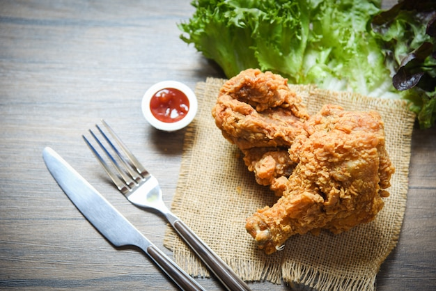 Fried chicken crispy on sack with fork knife ketchup and salad lettuce vegetable on dining table