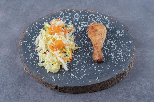 Coscia di pollo fritta e insalata su un pezzo di legno.