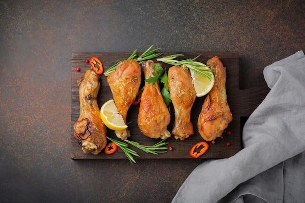 Fried chicken drumsticks on wooden cutting boardon a dark concrete