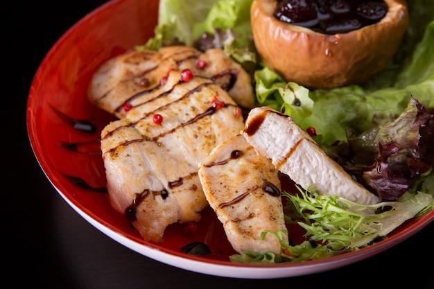 焼きチキンフィレ、焼きリンゴ、ソース、ハーブ、暗い背景の赤い皿の上
