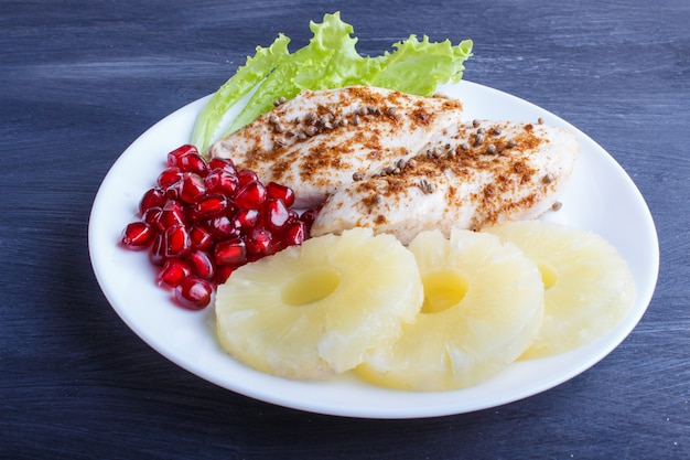 Fried chicken fillets with lettuce, pineapple and pomegranate seeds on black wooden background.
