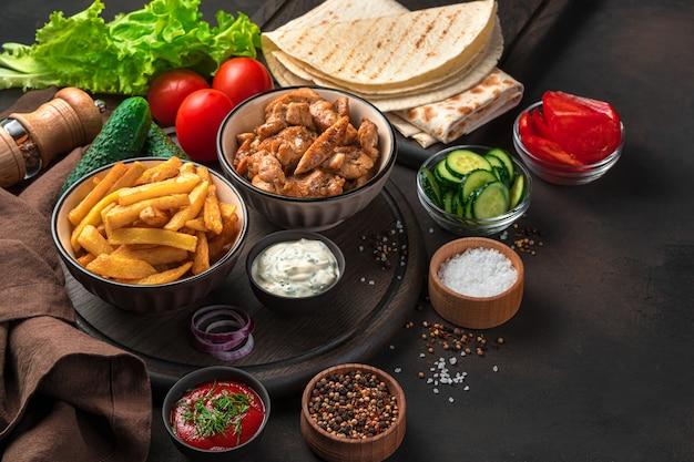 茶色の壁にフライド チキン、フライド ポテト、野菜、ソース、ピタパン、スパイス。シャワルマ、ブリトー、ジャイロの材料。ファストフード。