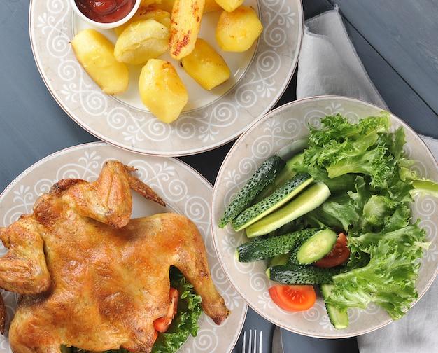 フライドチキン、フライドポテトとケチャップ、新鮮な野菜のサラダ