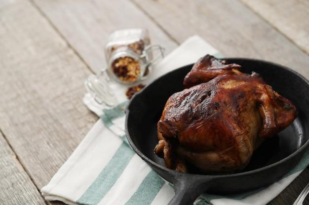 Жареный цыпленок на черной сковороде
