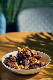 Жареный цыпленок в соусе чили с луком в белой тарелке. деревянный фон. китайская кухня