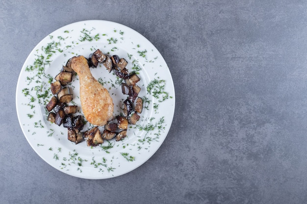 Coscia e melanzane di pollo fritte sul piatto bianco.
