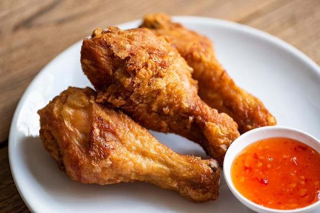 치킨 디핑 소스와 함께 접시에 프라이드 치킨 다리, 테이블 음식에 바삭한 프라이드 치킨