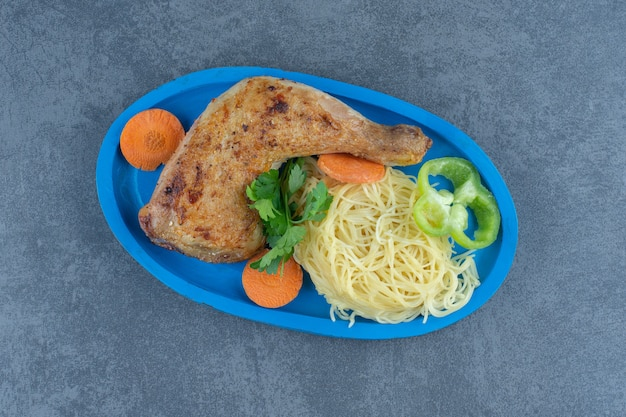 Fried chicken leg and spaghetti on blue plate.