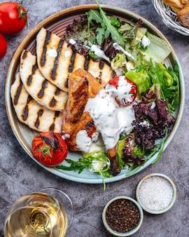 Жареная куриная ножка с соусом, подается с салатом руккола и помидорами гриль