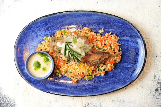 Fried chicken leg with bulgur, vegetables and creamy sauce