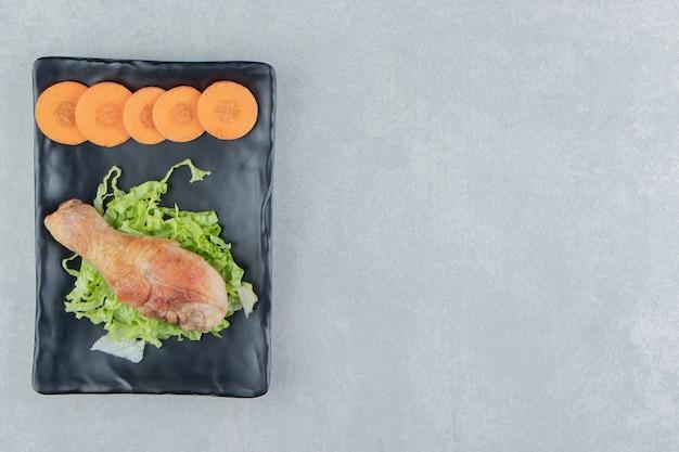 Жареная куриная ножка с нарезанной морковью и листьями салата.