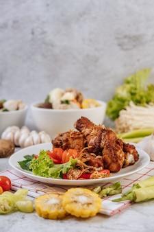 토마토, 칠리, 튀긴 양파, 양상추, 옥수수, 바늘 버섯을 곁들인 프라이드 치킨 다리.