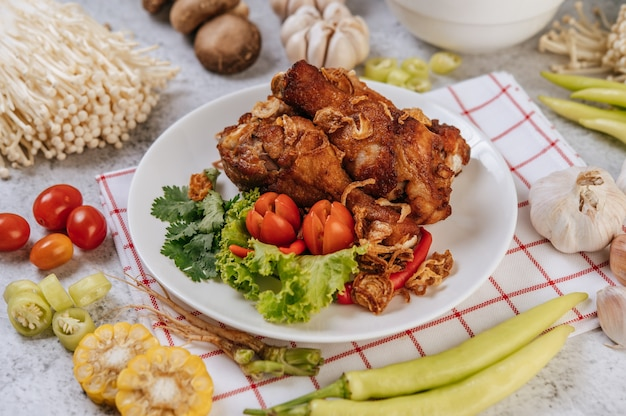 Жареная куриная ножка с помидорами, перцем чили, жареным луком, листьями салата, кукурузой и шампиньонами.