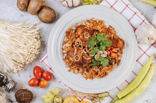 Coscia di pollo fritta con pomodoro, peperoncino, cipolla fritta, lattuga, mais e funghi agugliati.