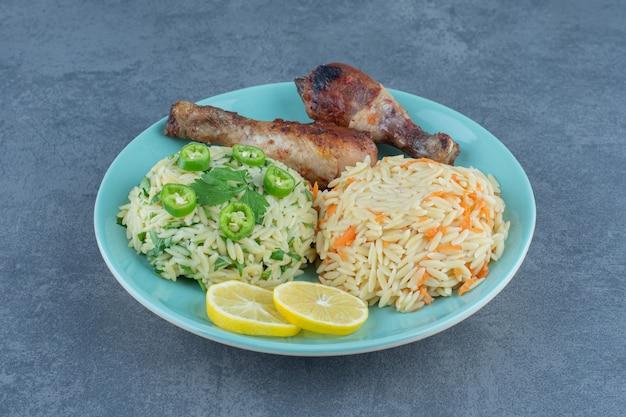 Жареные куриные окорочка и рис на синей тарелке.