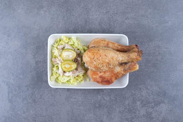 Жареные куриные ножки и салат на белой тарелке.