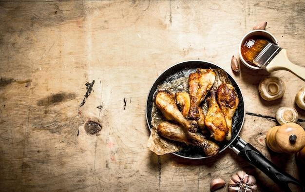 토마토 소스, 버섯, 마늘을 곁들인 프라이팬에 튀긴 닭 다리