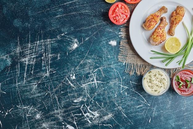 소스와 함께 하얀 접시에 튀긴 닭 다리.