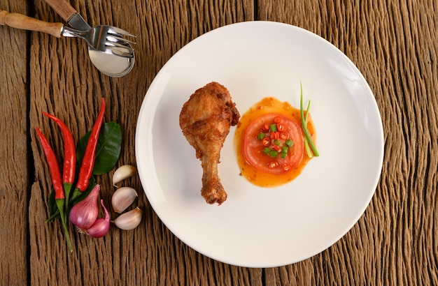 ソースとニンニク、エシャロット、唐辛子の白い皿にフライドチキンの足。