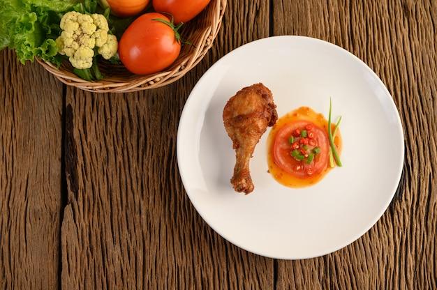 Жареные куриные ножки на белой тарелке с соусом.