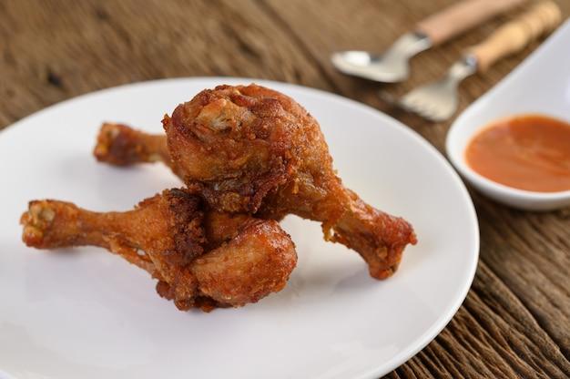 Жареные куриные ножки на белой тарелке с ложкой, вилкой и соусом.