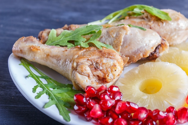 Fried chicken legs with arugula, pineapple and pomegranate seeds on black wooden background.
