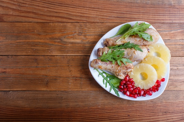 Fried chicken legs with arugula, pineapple and pomegranate seeds on brown wooden background.