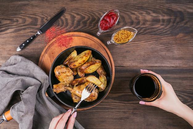木製のテーブルの上のフライパンでフライドポテトとフライドチキンの足。女性の手は赤ワインとフォークのグラスを持っています。上面図