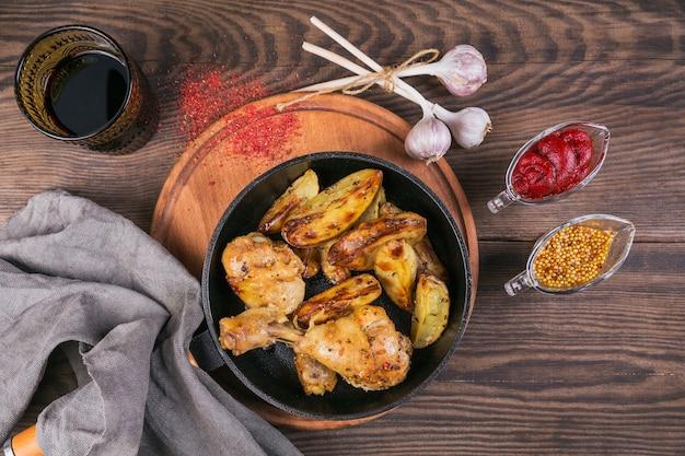 木製のテーブルの上のフライパンでフライドポテトとフライドチキンの足。フラットレイ
