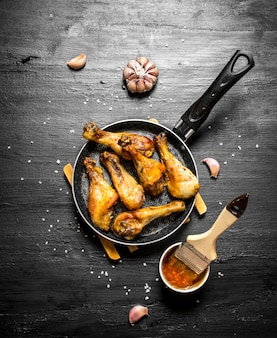 Fried chicken legs with garlic and sauce on a black wooden background