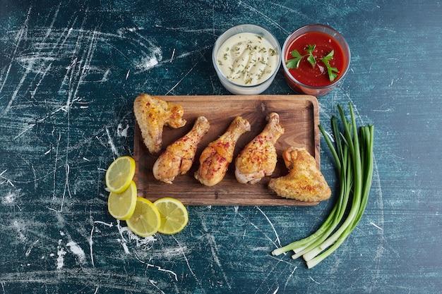 Жареные куриные окорочка с лимоном и луком на деревянной доске.